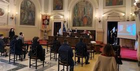 Aula magna dell'Ateneo con persone sedute distanziate che ascoltano