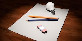 foglio di carta con sopra matite da disegno e lampadina