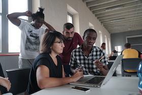studenti seduti ad un tavolo con un portatile aperto davanti