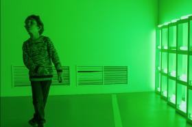 Bambino dentro una stanza dalle forti luci verdi